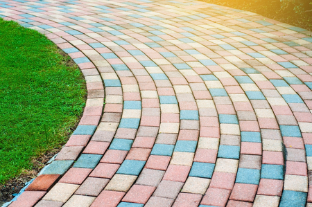 Colorful blocks created to curve walk way with green yard, beautiful curve path way in garden with light flare in morning.