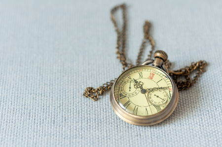 Golden vintage pocket watch with long strap on gray background, pocket watch time clock 10:10. Standard-Bild - 120931647