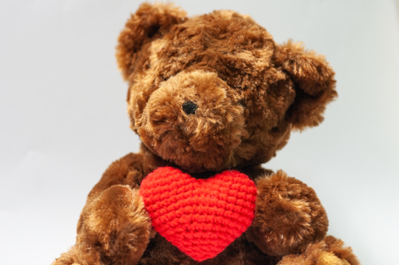 Cute dark brown bear holding wool red heart sitting on gray background, give love valentine lover concept. Banque d'images - 120934014