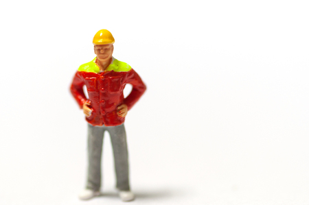 Selective focus miniature workers with yellow safety helmet and orange jacket uniform.  Industrail business conception.