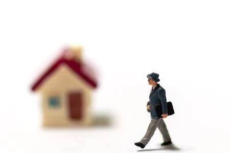 Selective focus miniature businessman in formal suit holding briefcase looking to blur small house red roof. Real estate agent survey for investment with house.