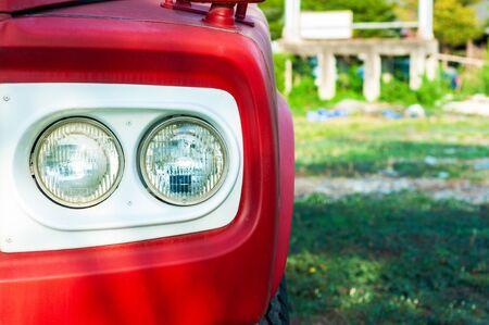 Klassischer roter LKW-Doppelscheinwerfer mit weißem Rahmen und grünem Hof hautnah,