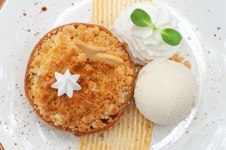 Classic crispy apple crumble with vanilla ice cream fresh whip cream and animal biscuit in beautiful plate. Pastries crispy desert.