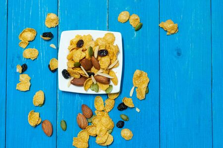 Cornflakes mix with almond rasin sunflower seeds on blue wooden plank.  Breakfast for children healthty food.