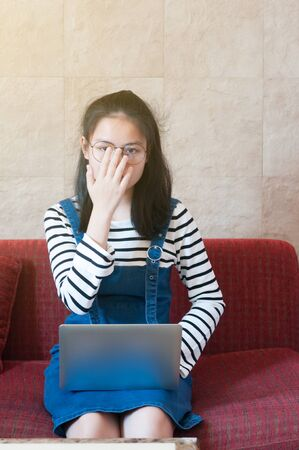 Asian teenager 16 years old using laptop sitting on red sofa and touch her glasses with right hand.
