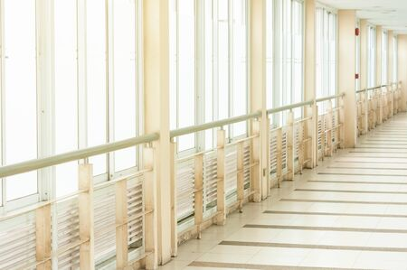 Long corridor, walkway connection between building,  empty walkway with windows and light flare. Stok Fotoğraf