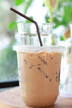 Fresh ice coffee in plastic glass on table with blur green plant background.  Relaxing life style with cold beverage. 스톡 콘텐츠