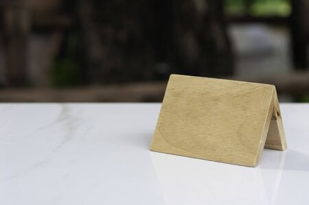 Blank wood reservation sign on marble table with blur background, blank sign for texting. Stock Photo