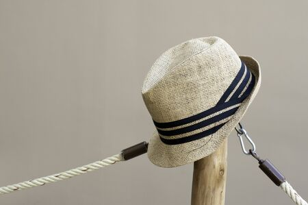 Vintage straw summer hat hanging top of wood pole and rope string, vintage fashion style and conception. Фото со стока
