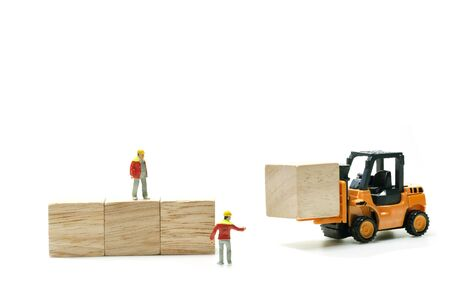 Insdustrial cargo storage business growth up conception, miniature leader and worker set up stack wooden cube block with forklift isolated on white background.