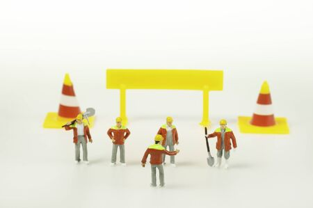 Foreman and worker Responsibility meeting next to traffic cone and caution sign to finish the project