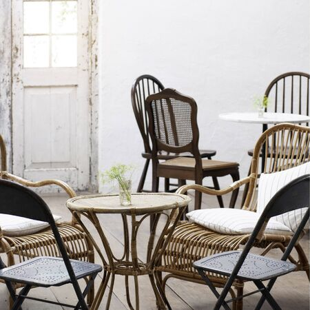 Interior living room vintage conception, rattan table and chair set in dinning room, classic house interior.