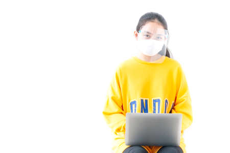 New normal life, Asian female teenager use 18 years old do online learning from home by laptop, woman wearing casual yellow cloth use laptop for work from home during corona virus crisis. Thailand.