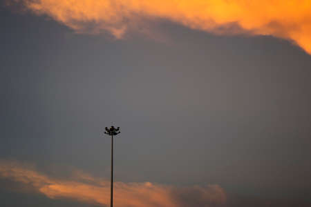 electricity post: Electricity post stand alone in front of orange clouds at twilight