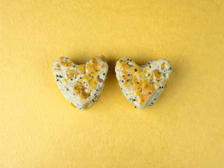 scone: 2 scone in heart shape on golden background. Stock Photo