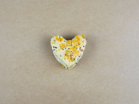 scone: Cookie scone in heart shape on brown paper background. Stock Photo
