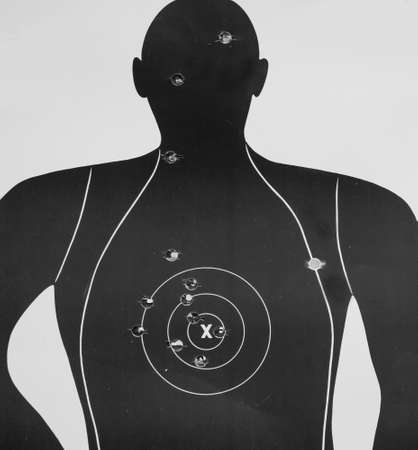 accurately: Bullet hole on black and white human shape target.