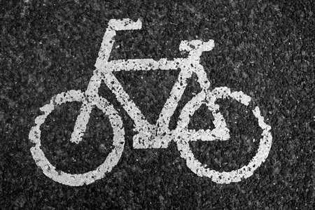 savety: Black and white close up of old bicycle sign on road.