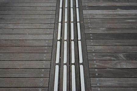 braille: bloque de metal en braille sobre suelo de madera.