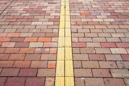 braille: Yellow braille block on side walk.