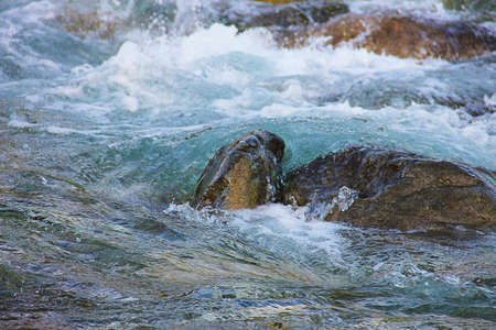 Stormy River: Waves crashing against a rock.