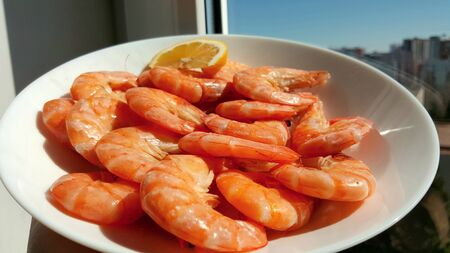 Kitchen and food, cooked shrimp, shrimp in a plate. Boiled shrimp with lemon. roasted prawns on white plate, top view. Stock Photo