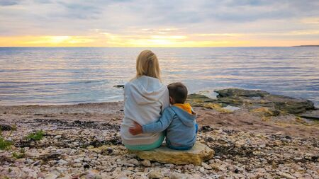 Mother and child on the beach. Mom and her baby are enjoying the sunset together. Family vacation by the sea. Standard-Bild