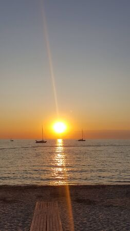 Sunset in the sea and the silhouette of the ship. View of the ship against the sunset. Sea beach sunset Sail. Sailing boat at sunset.