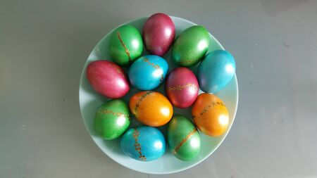 Colorful Easter eggs on a plate. Happy Easter holiday. The view from the top,