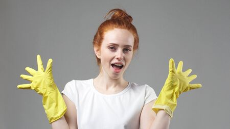 beautiful young maid in yellow rubber gloves, a smile, confidence, willingness to service, the concept of cleaning.