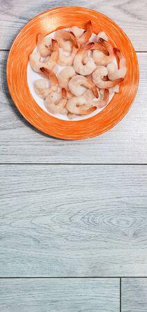 plate of frozen shrimp on a grey background. frozen peeled shrimp.