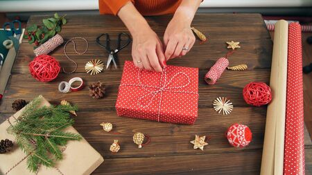 Primer plano de las manos de la mujer mientras envuelve el regalo de Navidad, sobre fondo de mesa de madera. Foto de archivo