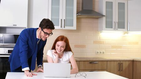 Young business couple talking and using laptop in kitchen at home. The concept of home business, freelance.