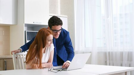 Business couple smiling working with laptop at home in kitchen.