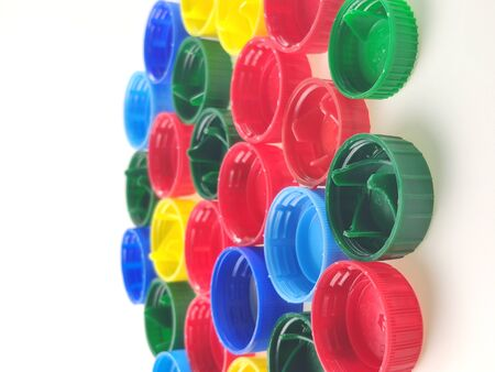 colorful plastic caps on white background, top view.