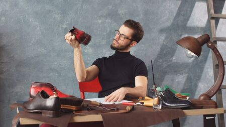 stunning young shoemaker with glasses is looking for defects in mens shoes. Zdjęcie Seryjne