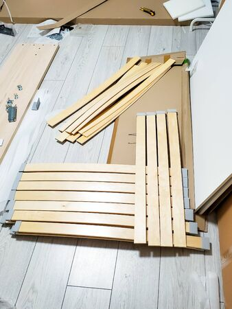 orthopedic wooden base and parts to assemble the bed in the room.