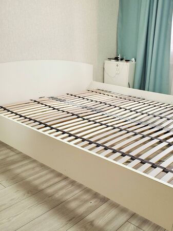 bed with orthopedic wooden base. assembling a bed in a room.