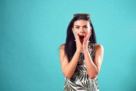cheerful girl with straight black hair with a surprised expression, posing on a blue background in the Studio.