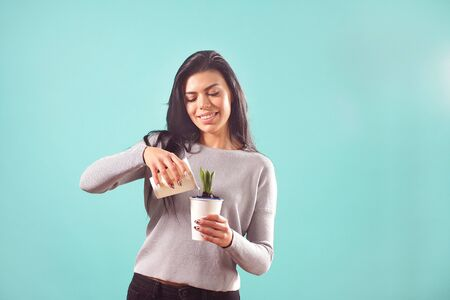 Cute girl watering a flower on an isolated blue background in the Studio.