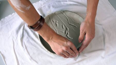 Close-up sculptor's hands that create a clay plate. Stockfoto