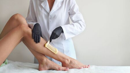 warm wax on womens feet, professional depilation hair removal in the Studio. Stock Photo