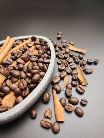 Scattered roasted coffee beans and a bowl of coffee and cinnamon on a black background close-up.
