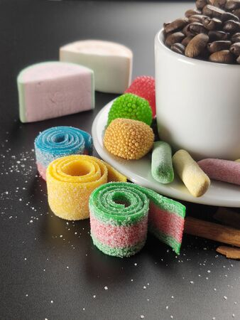 Colored sweets and a Cup with coffee beans on a black background.