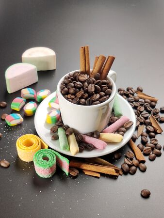 Cup with coffee beans and colored sweets on a black background. Stock fotó