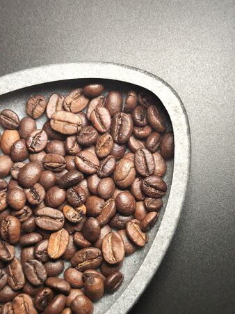 Roasted coffee beans in a bowl and on a black background.