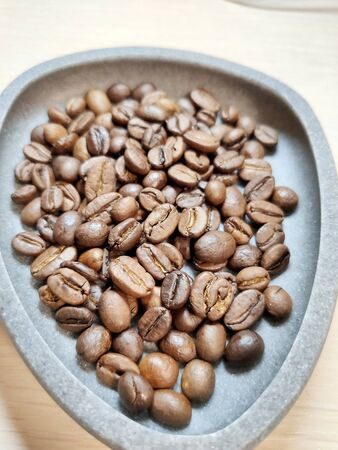Coffee beans in a gray bowl on a white background. Stock fotó