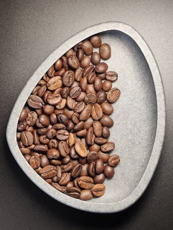 in a ceramic bowl, coffee beans on a black background. Stock fotó