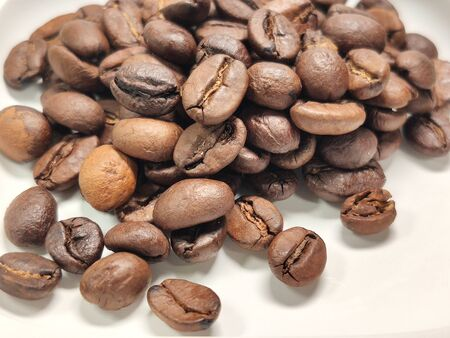 scattered roasted coffee beans on a white background close-up. Stock fotó