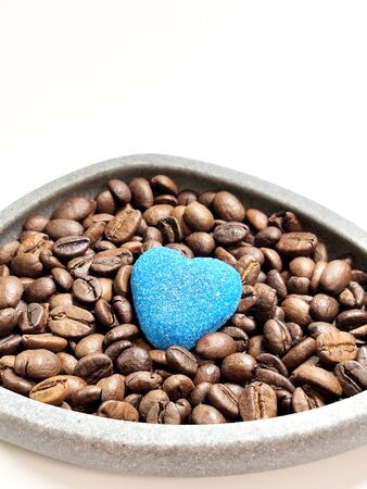 Coffee beans in a bowl and marmalade heart on a white background.